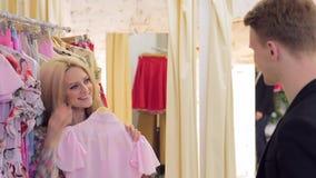La mujer rubia hermosa joven con su marido elige la ropa con una sonrisa almacen de metraje de vídeo