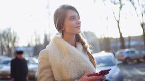 La mujer rubia hermosa joven está mecanografiando en su smartphone mientras que camina abajo de la calle muy transitada que pasa  almacen de video