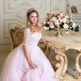 La mujer rubia hermosa que lleva el vestido magnífico y el cristal coronan la presentación en el apartamento clásico de lujo fotos de archivo