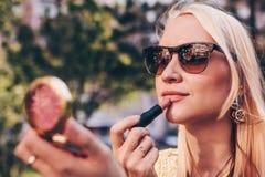 La mujer rubia hermosa que mira en un peque?o espejo y correcta compone Concepto correcto de la barra de labios imagen de archivo