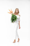 La mujer rubia hermosa que sostiene la zanahoria fresca con verde se va en el fondo blanco Salud y dieta Imagen de archivo
