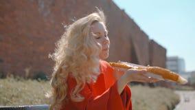 La mujer rubia hermosa Snacking en el parque con el bocadillo enorme apetitoso metrajes