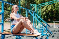 La mujer rubia joven atlética se sienta y descansa sobre campo de deportes durante sus vacaciones de entrenamientos imágenes de archivo libres de regalías