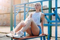 La mujer rubia joven atlética se sienta y descansa sobre campo de deportes durante sus vacaciones de entrenamientos imagenes de archivo