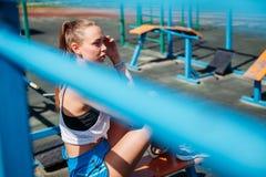 La mujer rubia joven atlética se sienta y descansa sobre campo de deportes durante sus vacaciones de entrenamientos fotografía de archivo libre de regalías