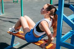 La mujer rubia joven atlética se sienta y descansa sobre campo de deportes durante sus vacaciones de entrenamientos fotografía de archivo