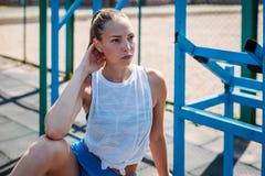 La mujer rubia joven atlética se sienta y descansa sobre campo de deportes durante sus vacaciones de entrenamientos fotos de archivo