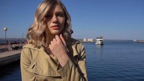 La mujer rubia joven atractiva en foso con la maleta del vintage se está sentando en el embarcadero de Jacht almacen de metraje de vídeo