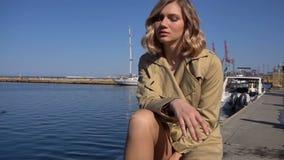 La mujer rubia joven atractiva en foso con la maleta del vintage se está sentando en el embarcadero de Jacht y está mirando en el almacen de metraje de vídeo