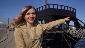 La mujer rubia joven atractiva en foso con la maleta del vintage se está sentando en el embarcadero y los puntos de Jacht en el m metrajes