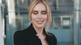 La mujer rubia joven atractiva en un equipo negro elegante parece derecha hacia la cámara y sonríe brillantemente Aeropuerto almacen de video