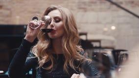 La mujer rubia joven atractiva huele el vino, gustos él, ella está satisfecha con el resultado Cenar, celebración Partido almacen de video