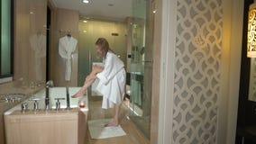 La mujer rubia joven atractiva mancha la loción del cuerpo en el cuarto de baño Muchacha hermosa que aplica la crema del skincare almacen de video