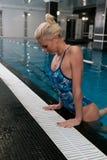 La mujer rubia joven atractiva sube fuera del agua en la piscina, inclinándose en el lado y mirando abajo Fotografía de archivo