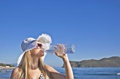 La mujer rubia joven bebe el agua Imagen de archivo