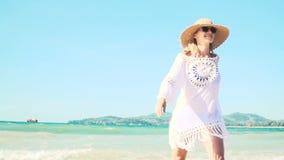 La mujer rubia joven con el sombrero y la túnica blanca se mueve en la playa tailandesa metrajes