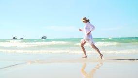 La mujer rubia joven con el sombrero y la túnica blanca se mueve en la playa tailandesa almacen de video