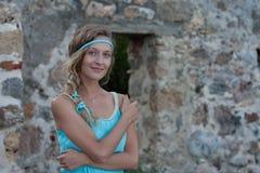 La mujer rubia joven con los ojos azules y trenzada oye el turq que lleva fotografía de archivo libre de regalías