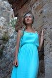 La mujer rubia joven con trenzado oye el vestido de la turquesa que lleva fotografía de archivo libre de regalías