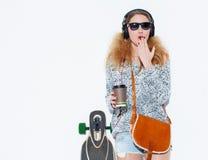 La mujer rubia joven de moda hermosa con un longboard, la taza de café y los auriculares frescos en sorpresa cubre su boca con el Fotografía de archivo