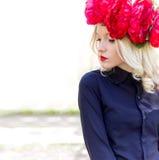 La mujer rubia joven elegante apacible joven hermosa con una corona roja de la peonía en una blusa negra camina en el manzanar en Imagenes de archivo