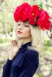 La mujer rubia joven elegante apacible joven hermosa con una corona roja de la peonía en una blusa negra camina en el manzanar en Imágenes de archivo libres de regalías