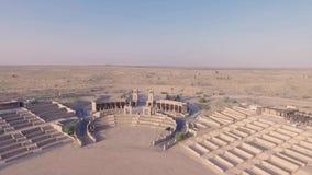 La mujer rubia joven elegante canta, juega música romántica en el piano digital blanco en arena o anfiteatro grande en desierto metrajes
