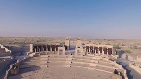 La mujer rubia joven elegante canta, juega música romántica en el piano digital blanco en arena o anfiteatro grande en desierto almacen de video