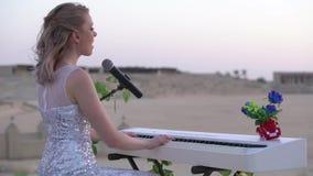 La mujer rubia joven elegante canta, juega música romántica en el piano digital blanco en arena o anfiteatro grande muchacha aden almacen de video