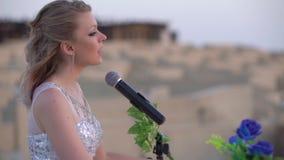 La mujer rubia joven elegante canta, juega música romántica en el piano digital blanco en arena o anfiteatro grande muchacha aden metrajes