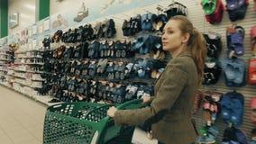 La mujer rubia joven elige la ropa en supermercado almacen de metraje de vídeo