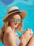 La mujer rubia joven en bikini un sombrero de paja por la piscina relaja vacaciones imágenes de archivo libres de regalías