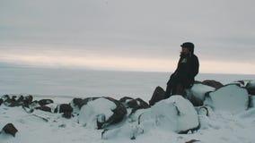 La mujer rubia joven en chaqueta y casquillo negros se sienta en piedras delante del mar congelado almacen de video