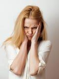 La mujer rubia joven en el gesto blanco del backgroung manosea con los dedos para arriba, cierre de presentación emocional aislad Foto de archivo libre de regalías