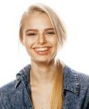 La mujer rubia joven en el gesto blanco del backgroung manosea con los dedos para arriba, cierre de presentación emocional aislad Imagen de archivo