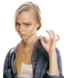 La mujer rubia joven en el gesto blanco del backgroung manosea con los dedos para arriba, cierre de presentación emocional para a Fotos de archivo