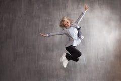 La mujer rubia joven en el traje de negocios y las zapatillas de deporte que saltaban para la alegría, gris texturizó el fondo fotografía de archivo libre de regalías