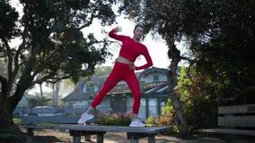 La mujer rubia joven en traje rojo del látex está haciendo ejercicios de la yoga en la tabla en el bosque almacen de metraje de vídeo