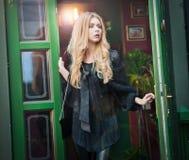 La mujer rubia joven encantadora en el equipo negro que presentaba en un verde pintó el marco de puerta Mujer joven magnífica atr Imagenes de archivo