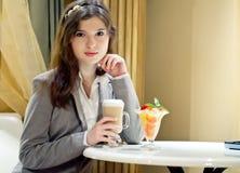 La mujer rubia joven está bebiendo el coffe Imágenes de archivo libres de regalías