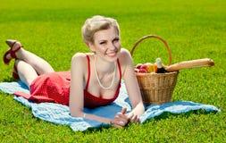 La mujer rubia joven está mintiendo en hierba Imagen de archivo libre de regalías