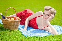 La mujer rubia joven está mintiendo en hierba Fotos de archivo