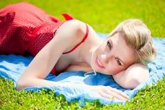 La mujer rubia joven está mintiendo en hierba Foto de archivo libre de regalías