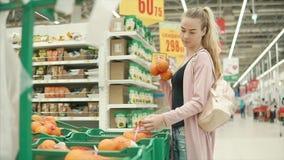 La mujer rubia joven está tomando los paquetes con las naranjas en un supermercado almacen de video