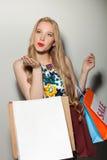 La mujer rubia joven hermosa ama hacer compras que va Fotografía de archivo
