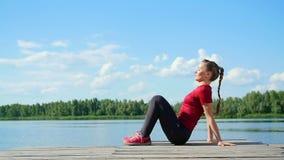 La mujer rubia joven hermosa, atlética que hace la coordinación y los ejercicios de la balanza, pectorales, oscilaciones presiona metrajes