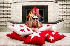 La mujer rubia joven hermosa que miente en la almohada en el cuarto con la chimenea y disfruta del fuego en la chimenea almohadas Fotografía de archivo