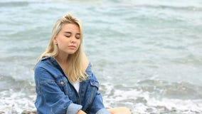 La mujer rubia joven hermosa que se sienta en la playa, la sonrisa linda y la mirada de la cámara en un fondo del mar agita almacen de metraje de vídeo