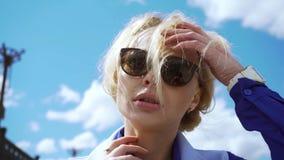 La mujer rubia joven imponentemente hermosa en un vestido blanco y gafas de sol tipo aviador hizo excursionismo por la sol metrajes