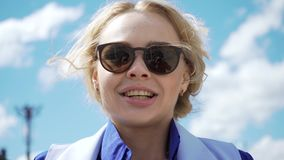 La mujer rubia joven imponentemente hermosa en un vestido blanco y gafas de sol tipo aviador hizo excursionismo por la sol almacen de video